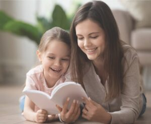 Nanny reading book with little girl