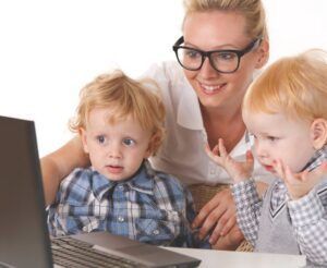 Nanny with glasses teache little kids with computer